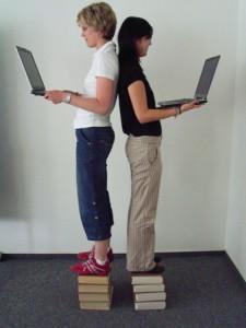 Zwei Studentinnen stehen auf Büchern mit Laptop in der Hand