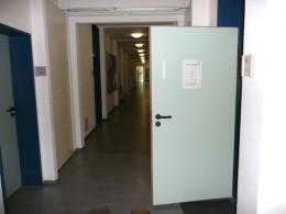 Zettel an der Tür mit Krankenhausflur
