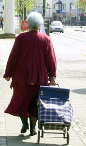 alte Frau von hinten mit Einkaufswagen