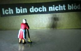 """Miniatur-Hausfrau vor Spruch """"Ich bin doch nicht blöd"""""""
