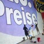 """Miniatur-Hausfrau steht  vor Wand mit Spruch """"k.o. Preise"""""""