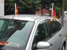 An einem Auto sind Deutschlandfahnen an den Türen befestigt