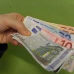Geldscheine in Hand auf grünem Hintergrund