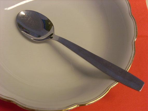 Leerer Suppenteller mit Löffel auf rotem Hintergrund