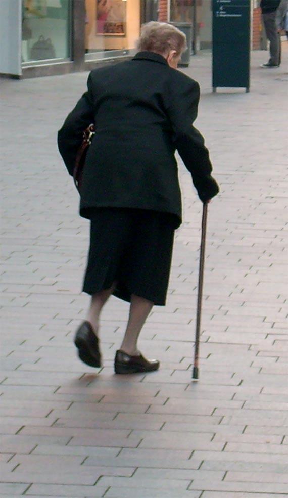 ältere Frau mit Stock als Gehhilfe