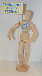 männliche Holzfigur hält Schild auf dem steht Feminismus gegen Freiheit