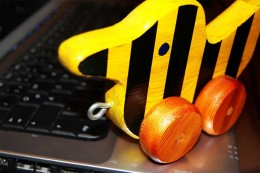 ElterngeldPlus gelbe Holzente auf laptop