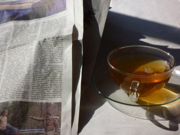 Tasse mit Tee und ein Stück Zeitung