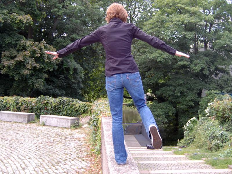 Frau balanciert auf einer Mauer