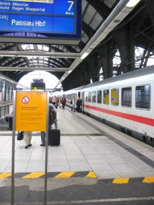 stehender Zug, rechts, im Vordergrund gelbes Schild