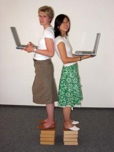 Zwei junge Frauen mit Laptop stehen auf je einem Bücherstapel