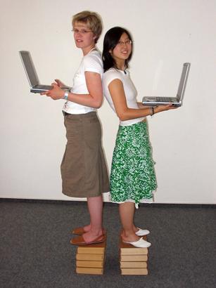Startup Monitor, Zwei junge Frauen mit Laptop stehen auf je einem Bücherstapel