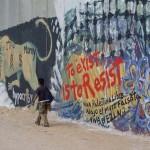 Junger Mann vor der bemalten Mauer in Bethlehem