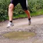 die Beine einer Läuferin beim Sprung über eine Pfütze