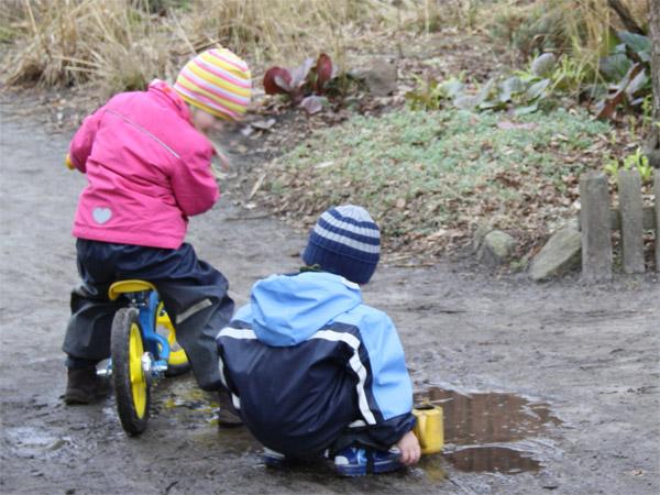 Kinder spielen in der Pfütze bei Regenwetter