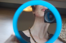 In einem Speigel ist der Gesichtsausschnitt einer Frau zu sehen