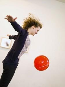 Junge Frau springt mit rotem Ball