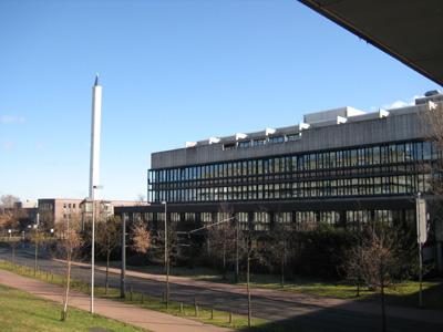 Links Turm mit Spitzdach, rechts Gebäude